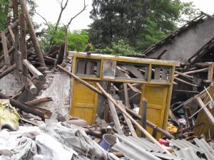 A single door frame bearing a portrait of Mao Zedong remained standing in a pile of debris along the road heading to Wenyuan, the epicenter of the 2008 Sichuan Earthquake